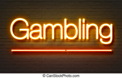 Gambling neon sign on brick wall background.
