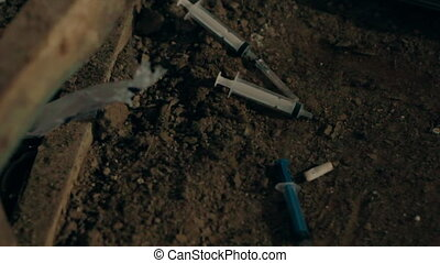 Syringes from drug addicts in the mud - Syringes from drug...
