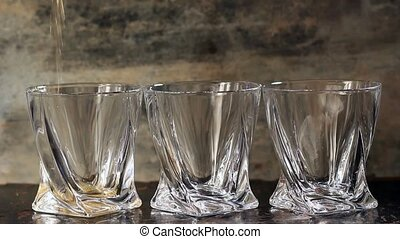 Pouring whiskey in three glasses