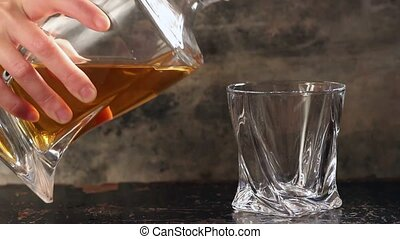 Pouring whiskey from bottle to glass over gray background