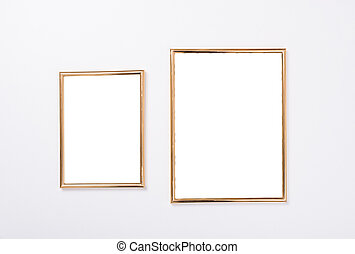 Two golden frames mock-up on white wall background, home...