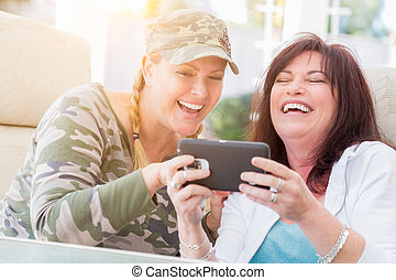 Two Female Friends Laugh While Using A Smart Phone on the...