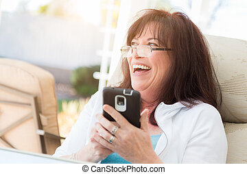 Attractive Middle Aged Woman Laughing While Using Her Smart Phone