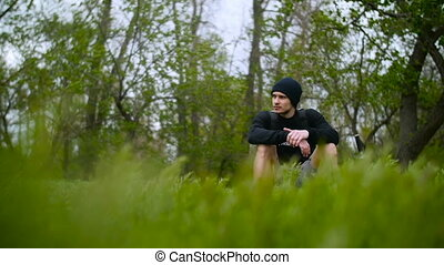 Young Man Sitting On Grass in Forest