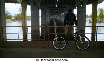 The Guy Is Resting Under A Bridge With A Bike. Urban...