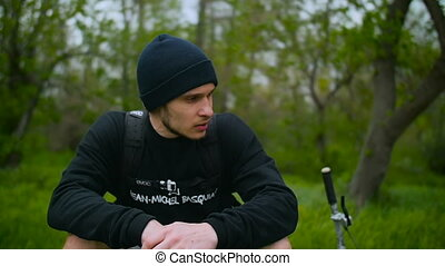 Tired Guy Is Resting On Grass With A Bike. Forest Background