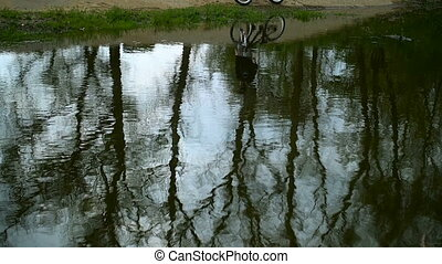 The Silhouette Of Biker Is Reflected In Water - The...