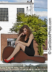 Woman with Guitar Case - Beautiful young woman sitting on a...