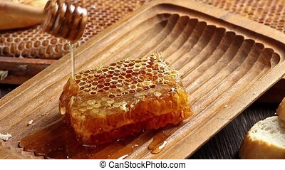 Honeycombs with pouring honey from wooden honey dipper
