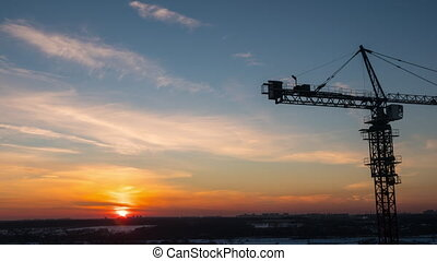 Timelapse with crane working on construction site on sunset...