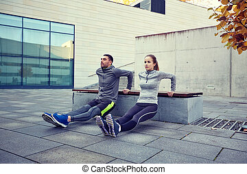 couple doing triceps dip exercise outdoors - fitness, sport,...