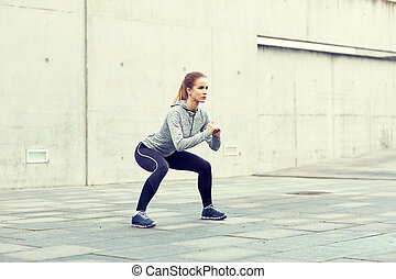 woman doing squats and exercising outdoors - fitness, sport,...