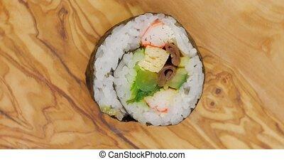 Sugoi sushi roll rotating on wood - Sugoi japanese sushi...