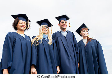 happy students or bachelors in mortarboards - education,...