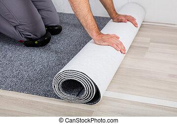 Worker's Hands Unrolling Carpet On Floor