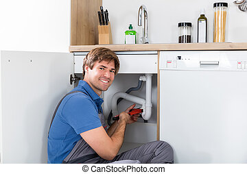 Male Plumber Fixing Sink Pipe With Adjustable Wrench In...