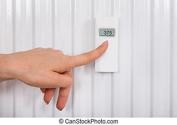 Person Adjusting Temperature With Digital Thermostat -...
