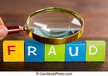 Person Hand With Magnifying Glass And The Word Fraud On...