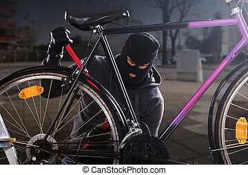 Thief Trying To Break The Bicycle Lock Parked Near The...