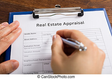 Person Hand Filling Real Estate Appraisal Form - Close-up Of...