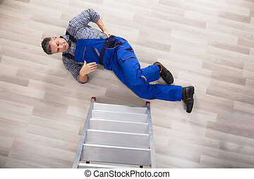 High Angle View Of A Repairman Fallen From Ladder - High...