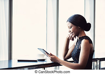 African woman smiling while holding and looking at a tablet...