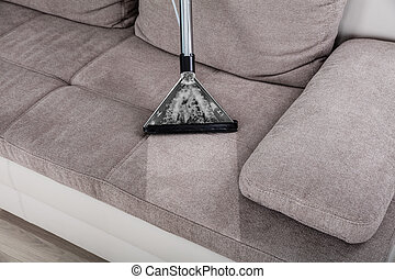 Woman Cleaning Sofa With Vacuum Cleaner - Closeup Of Woman...