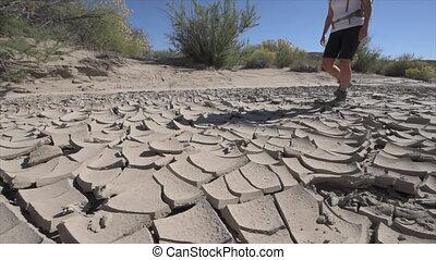 Desert Walk Hiker wallking on cracked desert - Hiker...