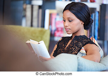 African American woman sitting comfortably on sofa while...