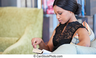 African woman turning page in her book seated on sofa -...