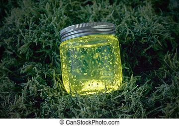 yellow glowing jar on the moss - Close yellow light glowing...