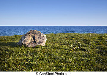 green hill near the sea - rock on the green grass hill near...