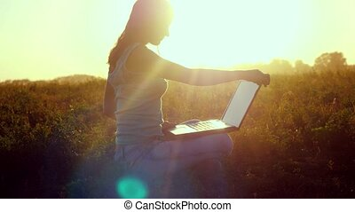 Young brunette woman typing on a laptop outdoors at beautiful sunset sitting on the grass with amazing lense flare effects in summer time.