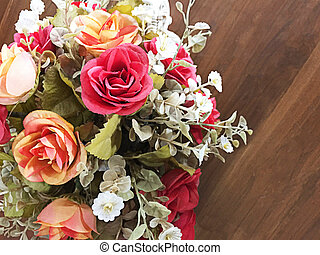 Bouquet of orange roses fake on a wooden table - Bouquet of...