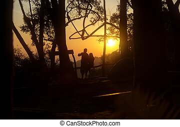 Silhouettes of sweetheart in love at sunrise.