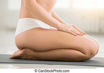 Young woman sitting in vajrasana pose, white color...