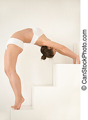 Young sexy attractive woman Standing Backward Bend, white...