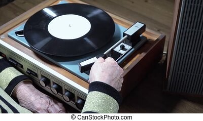 Old woman listening vinyl on player - Old women hands turn...
