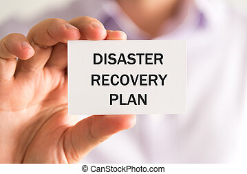 Businessman holding DISASTER RECOVERY PLAN card - Closeup on...