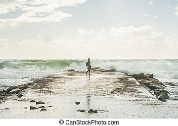 Silhouette of woman walking on pier at stormy Mediterranean sea