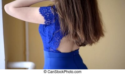 Girl with long hair in a blue lace dress fixes her hair and spinning. The frame is only hair and body. Close.Movement