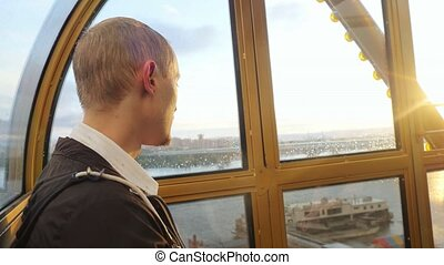 Young handsome man looking to the sun in a ferris wheel...