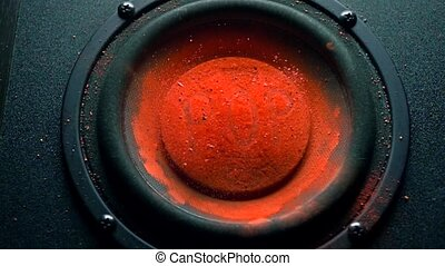 Pop inscription on orange powder over trembling speaker. Super slow motion shot