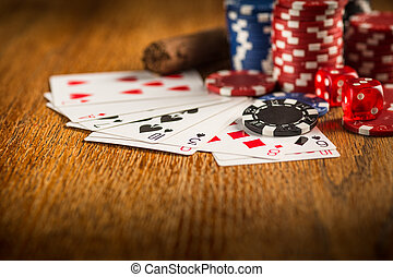 Cigar, chips for gamblings, drink and playing cards on...
