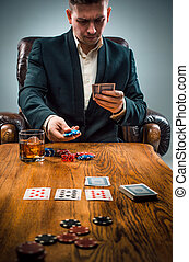 The man, chips for gamblings, drink and playing cards on...