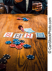 The chips for gamblings, drink and playing cards on wooden...