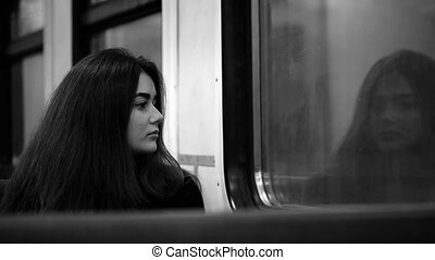 The girl rides in the train and looking out the window....