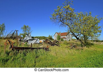 Family farm in ruins - A former family farm, machinery, and...