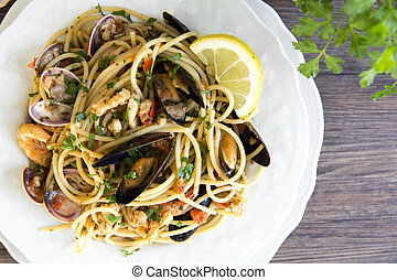 Spaghetti with seafood in white ceramic plate on wooden...