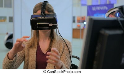 Young woman using virtual reality glasses - Exhibition of...